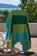 blue and green striped towel draped across back of deck chair echoes the colors of the view of Tortola from Jost Van Dyke