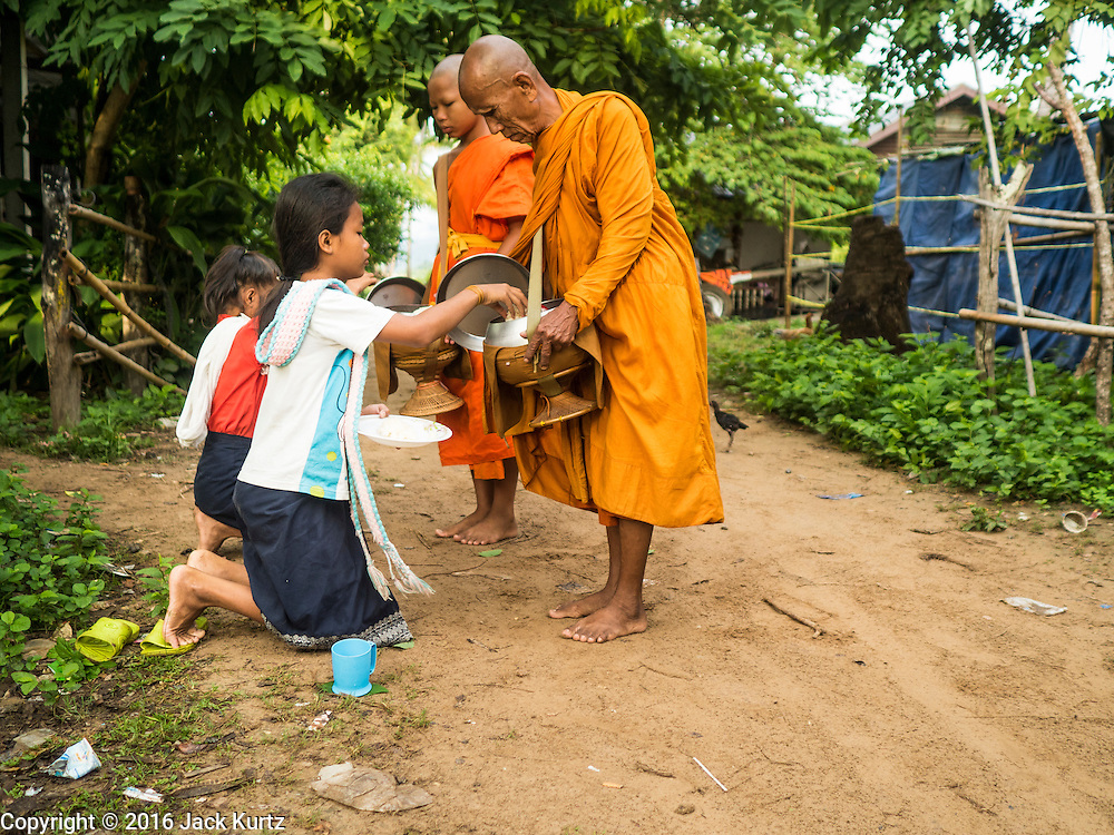 "20 JUNE 2016 - DON KHONE, CHAMPASAK, LAOS:  Girls present alms to monks from Wat Khone Nua on their morning alms' rounds, called the ""tak bat"" in Don Khone village on Don Khone Island. Don Khone Island, one of the larger islands in the 4,000 Islands chain on the Mekong River in southern Laos. The island has become a backpacker hot spot, there are lots of guest houses and small restaurants on the north end of the island.    PHOTO BY JACK KURTZ"
