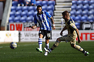 Jermaine Pennant of Wigan Athletic passes past Gaetano Berardi of Leeds United. Skybet football league championship match , Wigan Athletic v Leeds Utd at the DW Stadium in Wigan, Lancs on Saturday 7th March 2014.<br /> pic by Chris Stading, Andrew Orchard sports photography.