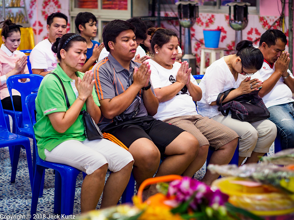 """14 FEBRUARY 2018 - BANG KRUAI, NONTHABURI, THAILAND: People pray before a resurrection ceremony at Wat Ta Khien, about 45 minutes from Bangkok in Nonthaburi province. The temple is famous for the """"floating market"""" on the canal that runs past the temple and for the """"resurrection ceremonies"""" conducted by monks at the temple. People lie in a coffin and ritualistically die before being reborn. Adherents believe it will improve their karma and help make up for past sins.         PHOTO BY JACK KURTZ"""