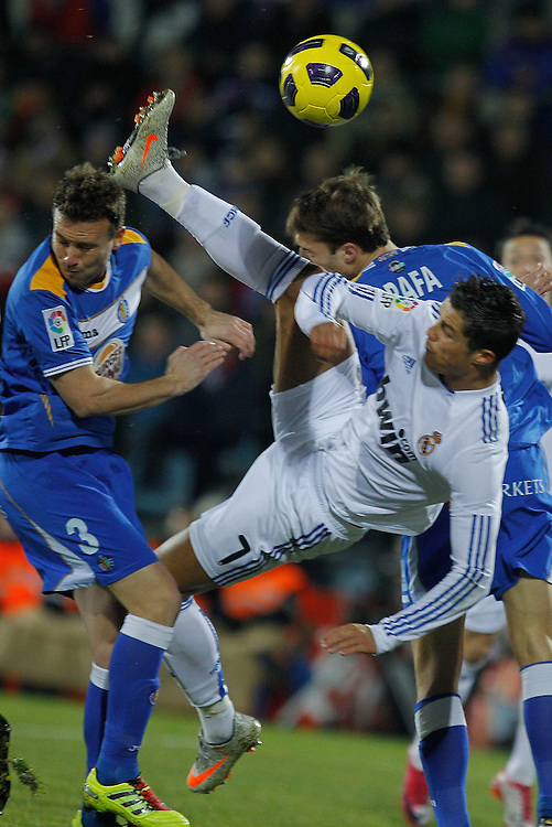 Real Madrid's Cristiano Ronaldo from Portugal, right, vies for the ball with Getafe's Jose Manuel Jimenez, left, during their La Liga soccer match at the Coliseum Alfonso Perez stadium in Getafe, near Madrid, on Monday, Jan. 3, 2011.