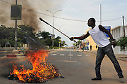 LOME, TOGO  13-05-23   - A man stokes a fire as opposition supporters clash violently with security forces in Lome, Togo on Thursday May 23, 2013.  Authorities have banned planned opposition protests in the capital city Lome this week after a crowd of protesting students smashed windows and torched cars on Tuesday.   Photo by Daniel Hayduk