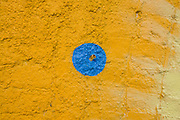 Painted blue spot on a yellow wall.