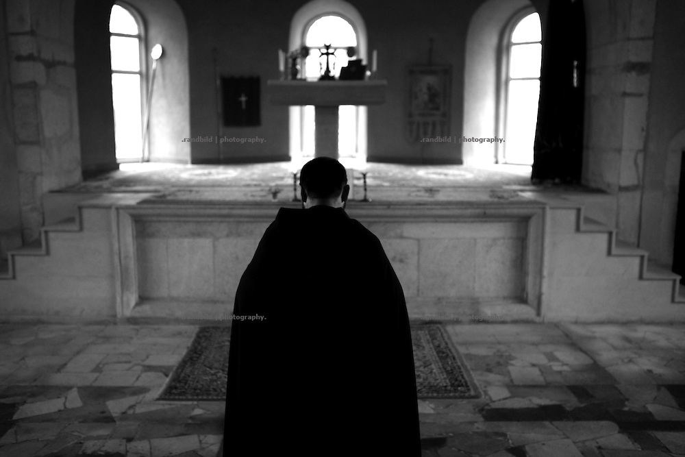 "A priest during a liturgy in Karabaghtots church.This image is part of the photoproject ""The Twentieth Spring"", a portrait of caucasian town Shushi 20 years after its so called ""Liberation"" by armenian fighters. In its more than two centuries old history Shushi was ruled by different powers like armeniens, persians, russian or aseris. In 1991 a fierce battle for Karabakhs independence from Azerbaijan began. During the breakdown of Sowjet Union armenians didn´t want to stay within the Republic of Azerbaijan anymore. 1992 armenians manage to takeover ""ancient armenian Shushi"" and pushed out remained aseris forces which had operate a rocket base there. Since then Shushi became an ""armenian town"" again. Today, 20 yeras after statement of Karabakhs independence Shushi tries to find it´s opportunities for it´s future. The less populated town is still affected by devastation and ruins by it´s violent history. Life is mostly a daily struggle for the inhabitants to get expenses covered, caused by a lack of jobs and almost no perspective for a sustainable economic development. Shushi depends on donations by diaspora armenians. On the other hand those donations have made it possible to rebuild a cultural centre, recover new asphalt roads and other infrastructure. 20 years after Shushis fall into armenian hands Babies get born and people won´t never be under aseris rule again. The bloody early 1990´s civil war has moved into the trenches of the frontline 20 kilometer away from Shushi where it stuck since 1994. The karabakh conflict is still not solved and could turn to an open war every day. Nonetheless life goes on on the south caucasian rocky tip above mountainious region of Karabakh where Shushi enthrones ever since centuries."