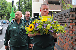 June 14, 2018 - London, UK - A paramedic carries flowers to Grenfell Tower on the first anniversary of the Grenfell Tower Fire in which 72 people were killed. Grenfell Tower caught fire on the night of June 14, 2017 after a small blaze started in one of the flats which spread rapidly up the outside of the 24-floor tower block. A public inquiry is currently underway. (Credit Image: © Rob Pinney/London News Pictures via ZUMA Wire)