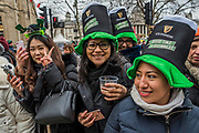 Visitors in many types of green hats are well wrapped up against the cold as they watch the parade go by -  the London St Patrick's Day parade from Piccadilly to Trafalgar Square.