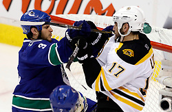 June 1, 2011; Vancouver, BC, CANADA; Vancouver Canucks defenseman Kevin Bieksa (3) shoves Boston Bruins left wing Milan Lucic (17) after a whistle during the first period in game one of the 2011 Stanley Cup Finals at Rogers Arena. Mandatory Credit: Jason O. Watson / US PRESSWIRE