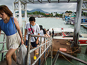 30 JULY 2013 - KOH SAMET, RAYONG, THAILAND:  Tourists get off a speedboat on the Thai mainland after leaving Koh Samet island Tuesday. About 50,000 liters of crude oil poured out of a pipeline in the Gulf of Thailand over the weekend authorities said. The oil made landfall on the white sand beaches of Ao Prao, on Koh Samet, a popular tourists destination in Rayong province about 2.5 hours southeast of Bangkok. Workers from PTT Global, owner of the pipeline, and up to 500 Thai military personnel are cleaning up the beaches. Tourists staying near the spill, which fouled Ao Prao beach, were evacuated to hotels on the east side of the island, which was not impacted by the spill. PTT Global Chemical Pcl is part of state-controlled PTT Pcl, Thailand's biggest energy firm.     PHOTO BY JACK KURTZ