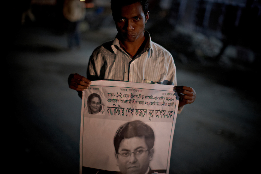 Political worker, Dhanmondi, Dhaka, Bangladesh...A worker of Awami league shows his candidate Sheikh Noor on a poster ahead of the general election...Bangladesh has finished with two years of emergency rule. The election results is compared to the landslide of 1970 that led to war and independence from Pakistan. .When preparations for the election started in late 2006, violent street-protests started, and led to a military backed interim government until the election happened under heavy security and watchful eyes on December 29th 2008...The past two years have seen a decrease of crime and corruption but also sparked violent student protests and curfews. Today  most people seem to be happy to return to some sort of normality. But in one of the poorest countries in the world where 80% live for less than a dollar a day, does it really matter who is in power? The circus is over, back to reality and putting food on the table...A blogger  from dhaka is quoted Ó we prefer messy democracy to military ruleÓ...Is this the end of night, a new dawn or yet another dusk?..Photo by: Eivind H. Natvig/MOMENT *** Local Caption ***