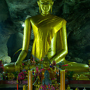 Main Buddha image at Krasae Cave (Tham Kra Sae) in Kanchanaburi, Thailand. The cave is located on the side of the death railway line made famous in second world war by allied POWs, overlooking the river below.
