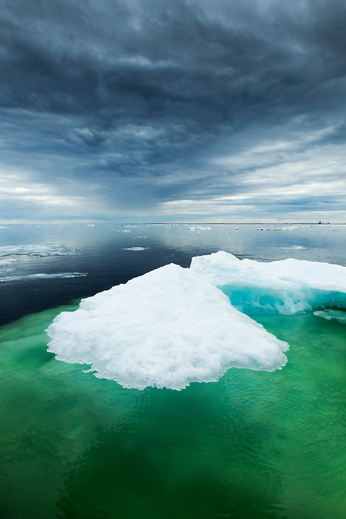Canada, Manitoba, Churchill, Storm clouds loom above melting iceberg on Hudson Bay on summer evening