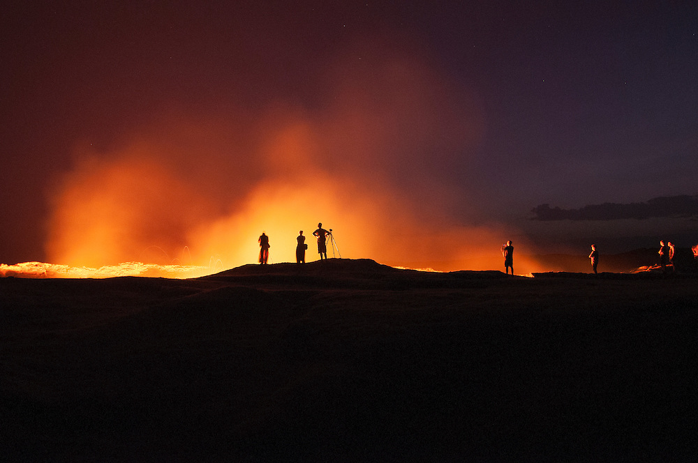 Photographers and travelers stand on the edge of Erta Ale, the only continuously active lava lake in the world. Erta Ale is located in northern Ethiopia near the Danakil Depression and is a shield volcano with a pit-crater of about 65m wide.