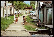 Kids play on sidewalk in Eirunepe slum; note ramps and stilts on homes for flooding; Amazonas Brazil
