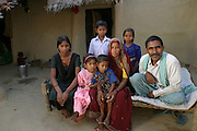 Yadav family portrait in the courtyard of their home during revisit with the family, 2004. Nishadevi (called Guddi, in green); Seema (in pink); Anurag (called Guddu, in white); Anil, held by his mother, Mishri, Aarti, in blue, and their father Bachau Yadav. Ahraura Village, Uttar Pradesh, India. The Yadavs were India's participants in Material World: A Global Family Portrait, 1994 (pages: 64-65), for which they took all of their possessions out of their house for a family-and-possessions-portrait. Child, Children. Work..
