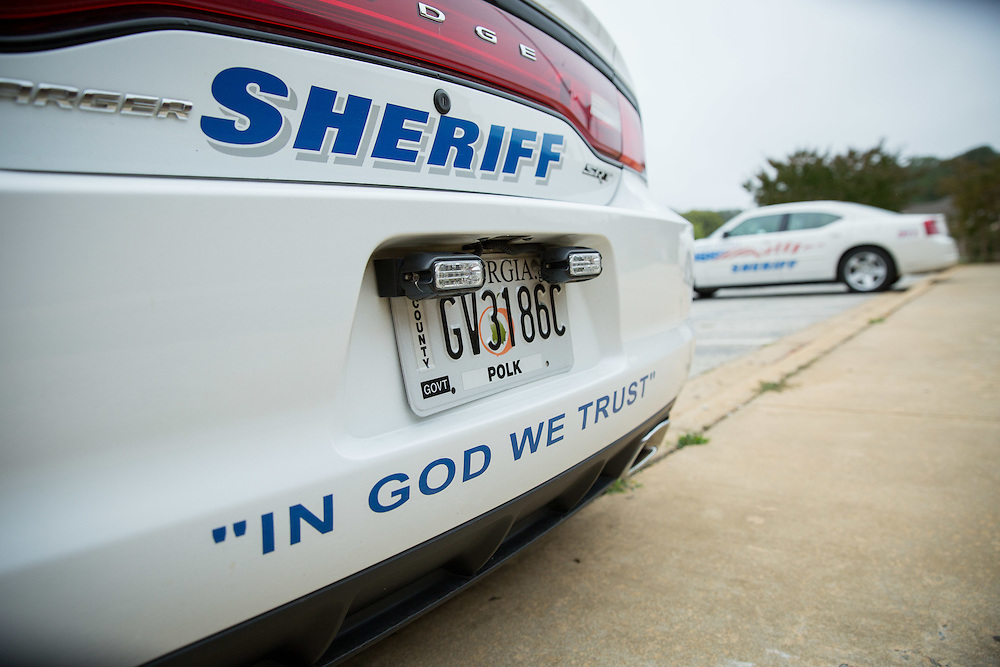 """Polk County Sheriff's Office vehicles, which have decals that read  """"In God We Trust"""" sit in the parking lot at the Polk County Public Safety Complex in Cedartown, Ga., on Thursday, Oct. 1, 2015. More than 50 departments across the country have done so in recent months. Photo by Kevin D. Liles for The New York Times"""