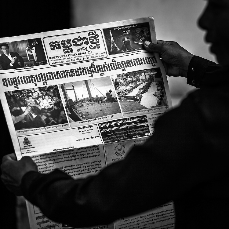 A woman reads the newspaper with images and stories of the previous days stampede outside Calmette Hospital where many of the victims were brought.