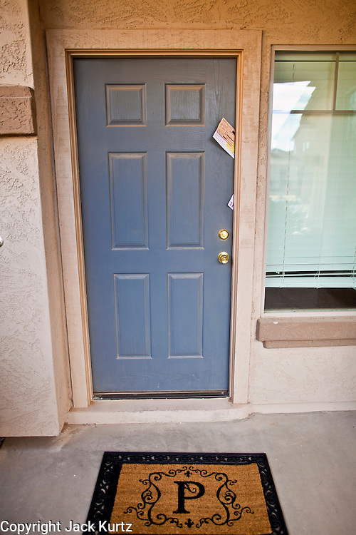 """26 DECEMBER 2010 - MARICOPA, AZ: The front door and welcome mat with P in front of the home BRISTOL PALIN, 20, bought in Maricopa, AZ, for $172,000. The former contestant on """"Dancing with the Stars"""" and daughter of Sarah Palin, former governor of Alaska, former Republican Vice Presidential candidate, reality television star, best selling author and supporter of the Tea Party movement. Bristol Palin paid $172,000 cash for the two-level, 3,900-square-foot, brown stucco house with a tile roof, 2 1/2 baths, a three-car garage, landscaped front and back yards, and access to a community pool. Local media reported that the home was built in 2006, at the peak of the Arizona real estate boom, and was bought for a little under $330,000 at the time. According to paperwork filed with the Pinal County Recorder's Office, Palin closed on the home in early December, buying it from Michael and Cynthia Smith, North Dakota investors who bought the home when it was in foreclosure. The home is in the Cobblestone Farms development in Maricopa, about 40 miles from Phoenix. Maricopa was a small farming community until the late 1990's when land speculators starting buying up the farms and turning them into subdivisions. Growth in Maricopa boomed from 2002 until 2008 when the recession, foreclosure and banking crisis hit. Since then it has had one of the highest foreclosure rates in the United States. Now investors are starting to buy foreclosed homes in Maricopa, anticipating the end of the foreclosure crisis. Homes in Maricopa are now selling for about less than half of what they cost in 2006. Bristol Palin has not commented publicly on the purchase and has not said if the home is an investment or if she plans to live in it. Photo by Jack Kurtz"""