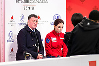 KELOWNA, BC - OCTOBER 25:  Russian figure skater Evgenia Medvedeva sits with former champion figure skater and now coach, Brian Orser and awaits her score at Skate Canada International in the ladies short program at Prospera Place on October 25, 2019 in Kelowna, Canada. (Photo by Marissa Baecker/Shoot the Breeze)