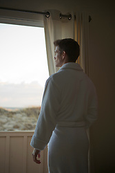 man in a white bathrobe standing in a doorway overlooking the beach in The Hamptons