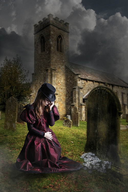 Girl in a churchyard kneeling by a grave