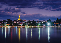 KYAING TONG, MYANMAR - CIRCA DECEMBER 2017:  View of lake Nong Tung and Wat Noi Naw in Kyaing Tong at night.