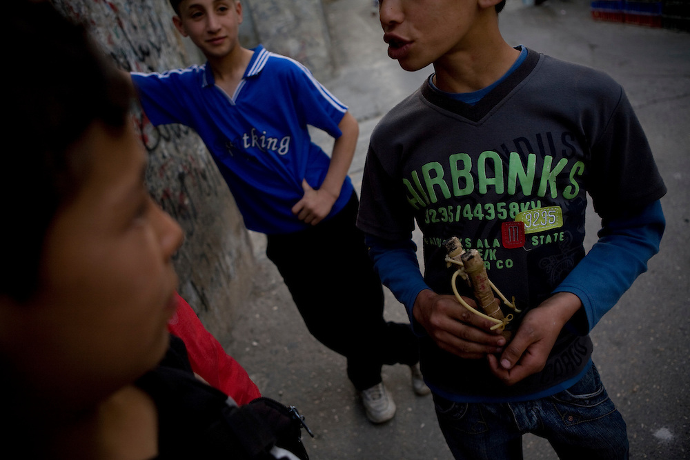 Children hang out on a street corner in Aida refugee camp near the town of Bethlehem, West Bank, Wednesday 14th May 2008.