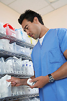 Male nurse standing by shelves with medical supply, low angle view