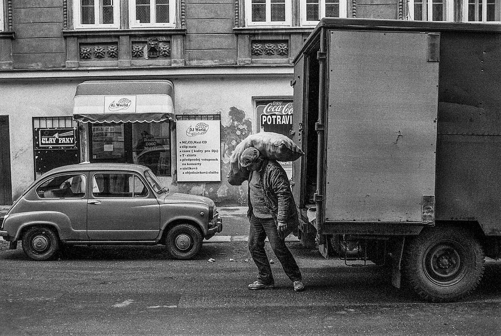 A man is unloading a truck with potatoes in Borivojova street.
