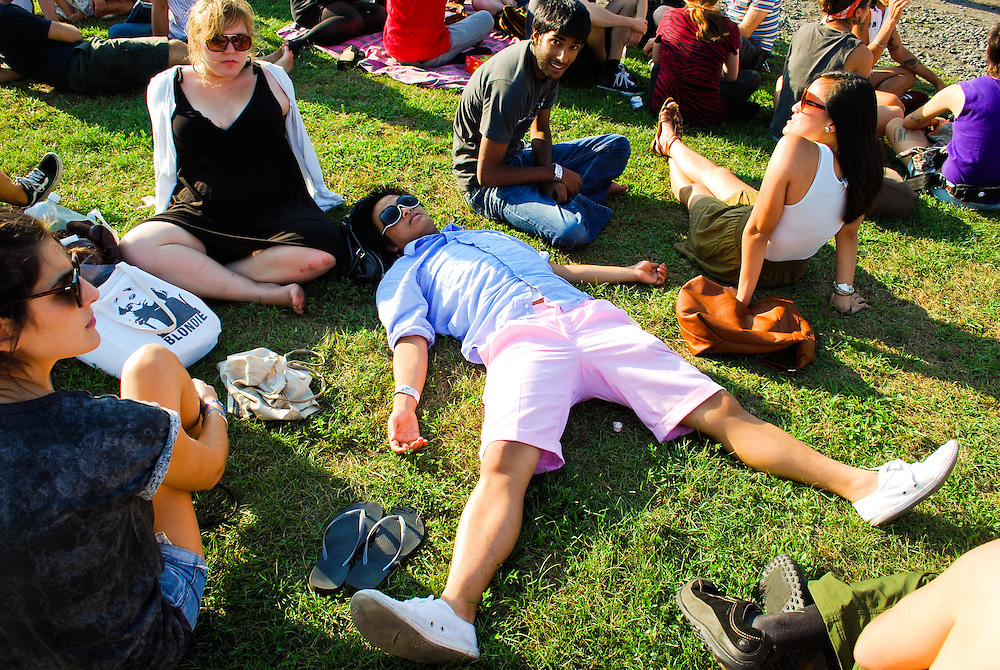 A concert goer lays spread eagle in the grass at the JELLY Pool Party free concert series East River State Park, Williamsburg, Brooklyn, New York