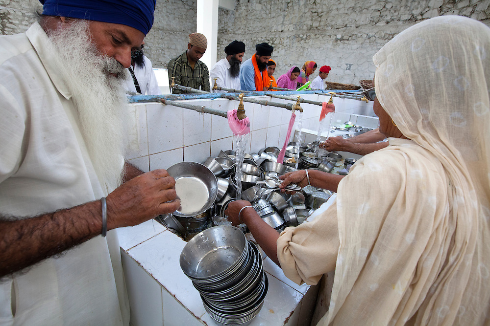 Sikh believers volunteer to clean the dishes at a Sikh kitchen,Langar. Some Langars serve tens of thousand free meals per day and the main kitchen workers are pilgrims.