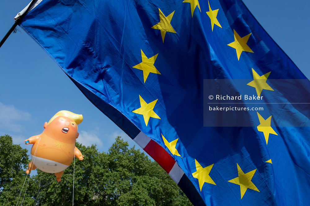 The inflatable balloon called Baby Trump flies above the European Union flag in Parliament Square in Westminster, the seat of the UK Parliament, during the US President's visit to the UK, on 13th July 2018, in London, England. Baby Trump is a 20ft high orange blimp depicting the US President as an enraged, smartphone-clutching infant - and given special permission to appear above the capital by London Mayor Sadiq Khan because of its protest rather than artistic nature. It is the brainchild of Graphic designer Matt Bonner. (Photo by Richard Baker / In Pictures via Getty Images)