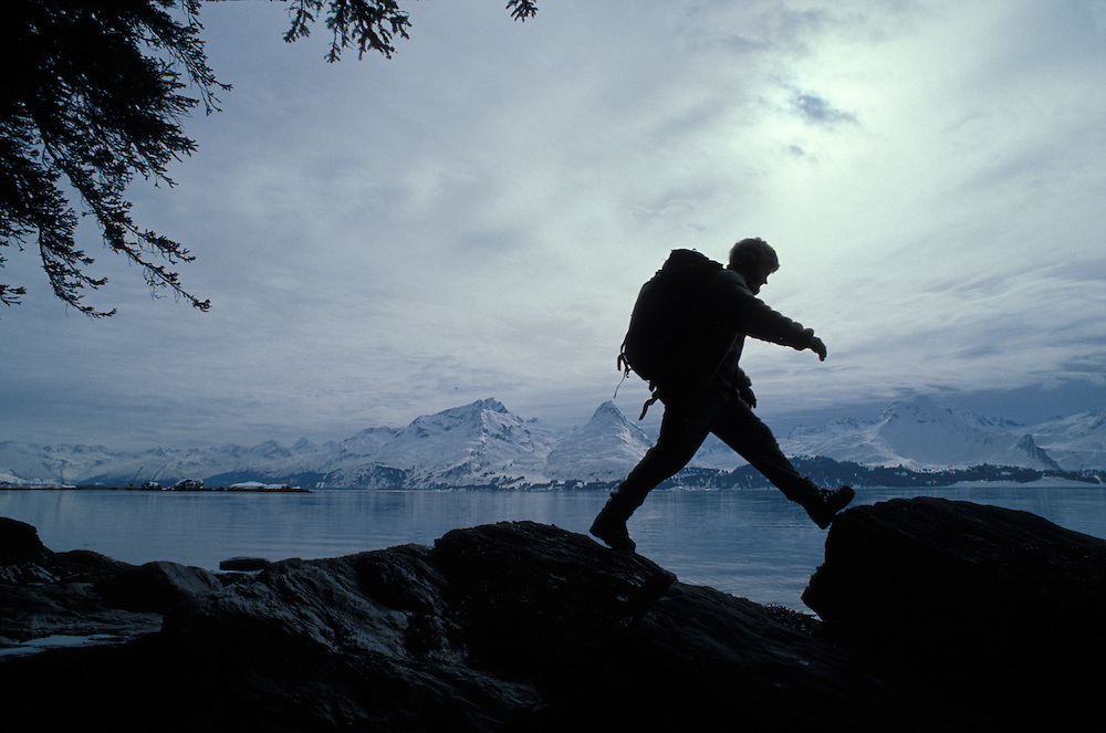USA, Alaska, Climber hikes along Prince William Sound with Chugach Mountains in distance near town of Valdez