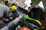 Inspecting the interior of a stretch limousine after a London Fire Brigade's 'extrication' team with the Vehicle and Operator Services Agency (VOSA) gave a demonstration on how firefighters rescue passengers by cutting open with dedicated cutting equipment a stretch limousine in London's Covent Garden Piazza. Highlighting the dangers of hiring illegal luxury or novelty cars, this vehicle was seized last year with many mechanical defects rendering it unsafe for those inside with limited exit doors. Of 358 cars stopped in March 2012, 27 were seized and 232 given prohibitions. This scenario is a simulation and therefore reproduces the reality of an emergency, using real emergency services personnel and equipment. Casualties are volunteers and none were injured in the making of this photograph.