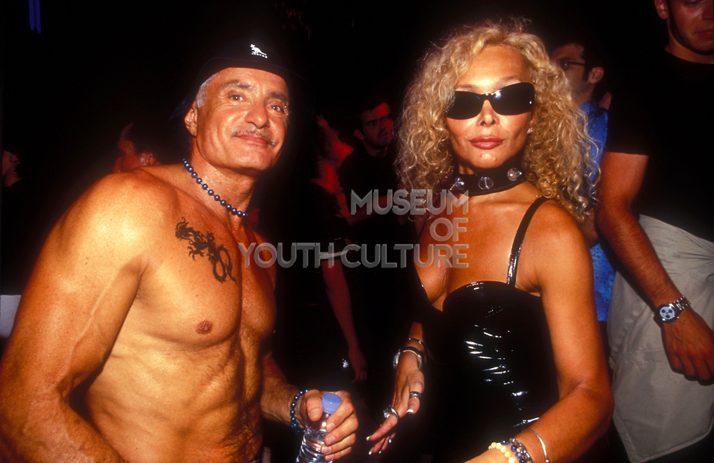 A sexy middle-aged couple at a night club. muscular man with a chest tattoo and woman wearing black leather dress, sunglasses and choker.