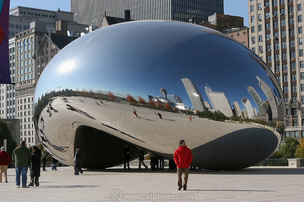 A large mirroring metal sculpture called The Cloud Gate, at Millennium Park, Chicago, Il, bends the cityscape, and people that pass by. USA. By British artist Anish Kapoor.