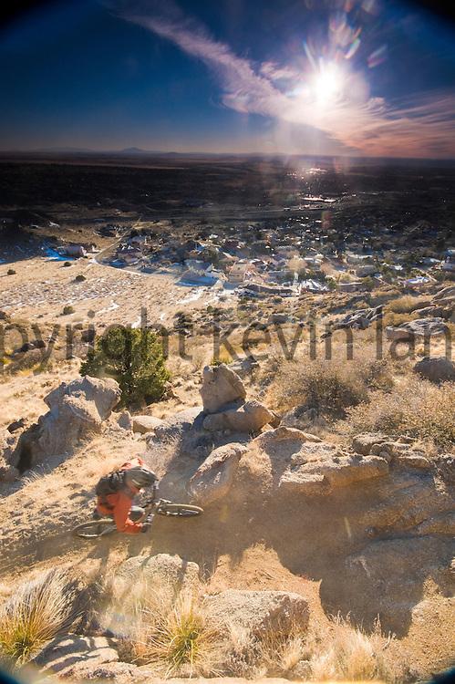 mountain biker on the high desert landscape.  sandia mountains above albuquerque, new mexico.