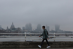© Licensed to London News Pictures. 07/01/2017. LONDON, UK.  A man walks over Waterloo Bridge during misty and foggy weather this morning. The weather in London today is misty, foggy and much milder than it has been during the past week.  Photo credit: Vickie Flores/LNP