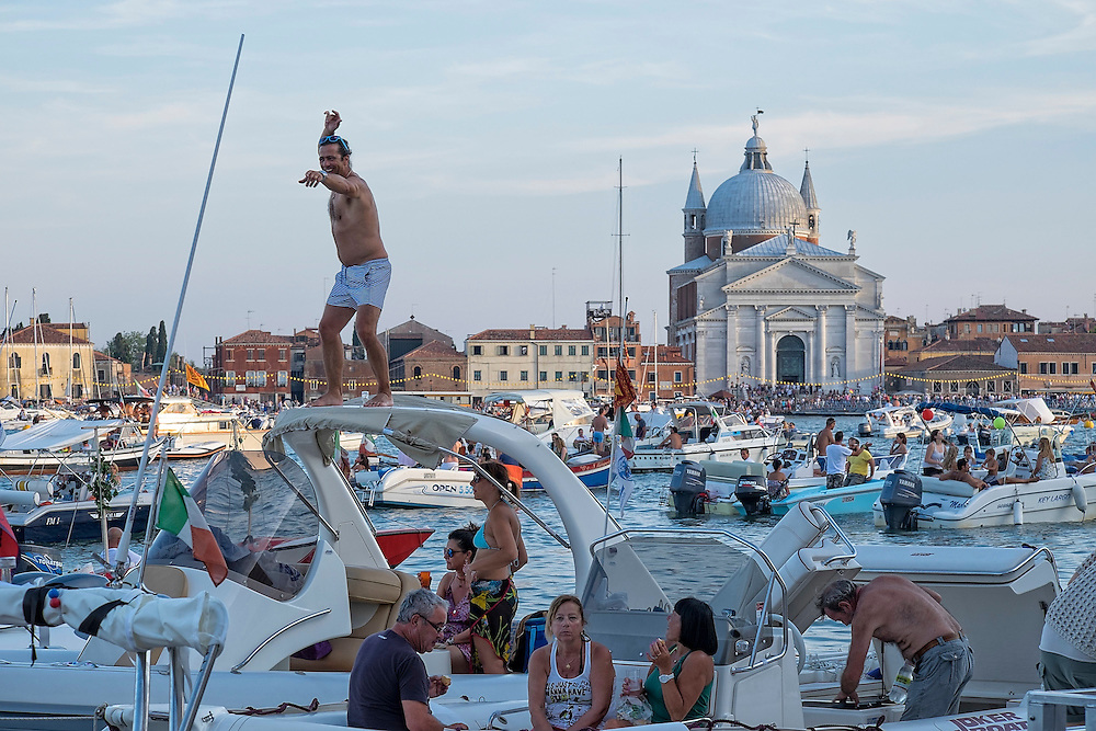 VENICE, ITALY - JULY 19:  A reveller dance on top of his power boat with the background of the Redentore Church on July 19, 2014 in Venice, Italy. Redentore , which is in remembrance of the end of the 1577 plague, is one of Venice's most loved celebrations. Highlights of the celebration include the pontoon bridge extending across the Giudecca Canal, gatherings on boats in the St. Mark's Basin and a spectacular fireworks display.  (Photo by Marco Secchi/Getty Images)