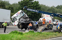 © Licensed to London News Pictures. 26/08/2017. Milton Keynes, UK. The lorry being recovered (left) and part of the remains of the minibus (pictured right on recovery vehicle) The scene on the M1 motorway near Milton Keynes after a crash involving a minibus and two lorries. Police say that several people are dead and four others have been taken to hospital after the accident on the southbound carriageway in the early hours of this morning. Photo credit: Ben Cawthra/LNP