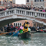 VENICE, ITALY - FEBRUARY 20:  Boats from from several rawing association reach a Ponte delle Guglie bridge and sail along the Cannaregio Canal during the Venetian Feast on February 20, 2011 in Venice, Italy. During the Venetian Feast a traditional water parade sails from San Marco along the Canal Grande to the  district of Cannaregio where there the crowd waits for the Svolo della Pantegana  (flight of the mouse).