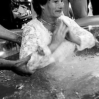 "Woman during the baptism. France, Marville, August 2002 - 40,000 Gypsies from all over the Europe come together and pray in Marville, a little village in France. They encamped in a former air base of NATO during 1 week. ""Vie et Lumiere"" is an International Evangelic Community. ©Jean-Michel Clajot / Cosmos"