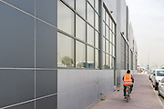 DUBAI, UAE - APRIL 30, 2016: A worker is cycling by Alserkal Avenue in Dubai' Al Quoz Industrial Area.