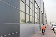DUBAI, UAE - APRIL 30, 2016: A worker is cycling by Alserkal Avenue in Dubai' Al Quoz Industrial Area.