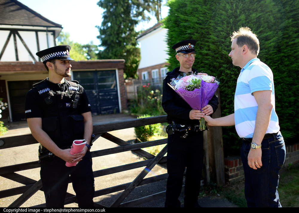© Licensed to London News Pictures. 07/09/2012. Claygate, UK A neighbour hands police flowers. The family home of Saad al-Hilli in Claygate, near Esher. Three members ofof the family have been shot dead in the French Alps. Photo credit : Stephen Simpson/LNP