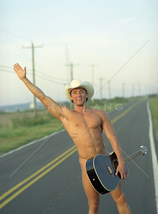naked muscular man smiling and waving on a road