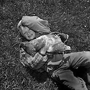 Boy with hen in the grass, Bursche mit Huhn liegt im Gras, garçon avec poule dans le pré. 2004. © Romano P. Riedo