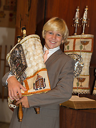 good looking blond Bar Mitzvah boy holding a Torah