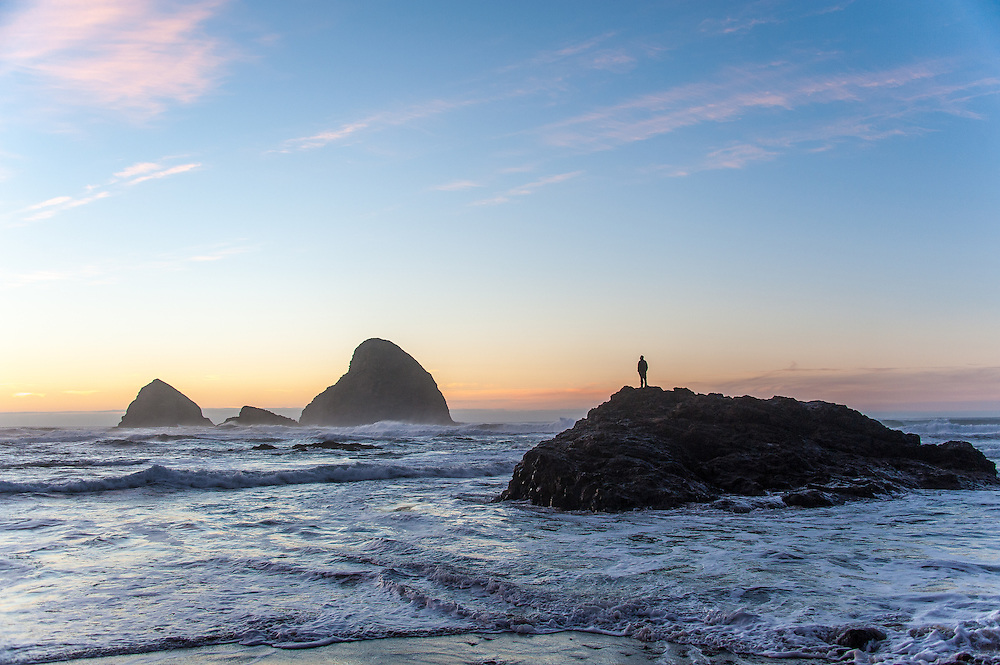 Man standing on a rock as the tide comes in at sunset on Oceanside Beach near Tillamook, Oregon.