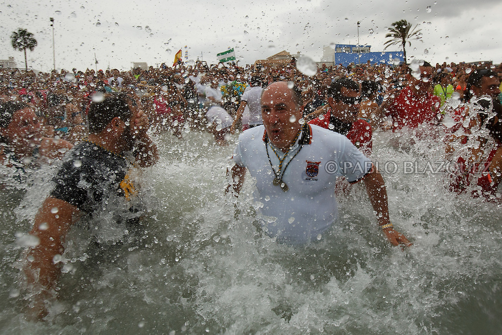 15/08/2016. Worshippers splash water to each other to cerebrate the arrival of the Virgin of Palm image during the yearly Virgin of Palm maritime pilgrimage at el Rinconcillo beach on August 15, 2016 in Algeciras, Spain. The Our Lady of Palm maritime pilgrimage in Algeciras dates back to 1975 and takes place annually when fishermen rescue the submerged virgin from the deep sea. Worshippers amid thousands of visitors await its arrival at the Rinconcillo beach. The devotion for the Virgin of Palm comes from the seventeenth century when a ship coming from Italy docked at Algeciras port to wait out bad weather. According to legend, once the crew of the ship removed a box with an image of the Virgin from its cargo the weather turned and the sea's tides were calmed. (© Pablo Blazquez)