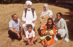 Family group with three generations sitting outside in garden,